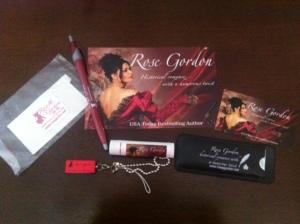 Signed postcard, screen cleaner, pen, lip balm, USB drive and bandage dispenser.