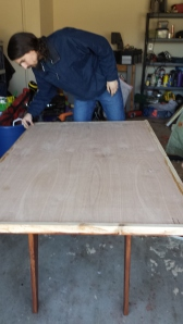 This was the table top after we turned it back over and put a rim around the edge. It wasn't exactly even (the boarder) which meant a lot of sanding and planing. As you can see, Bob is inspecting my work… He soon told me to keep going, it needed more.